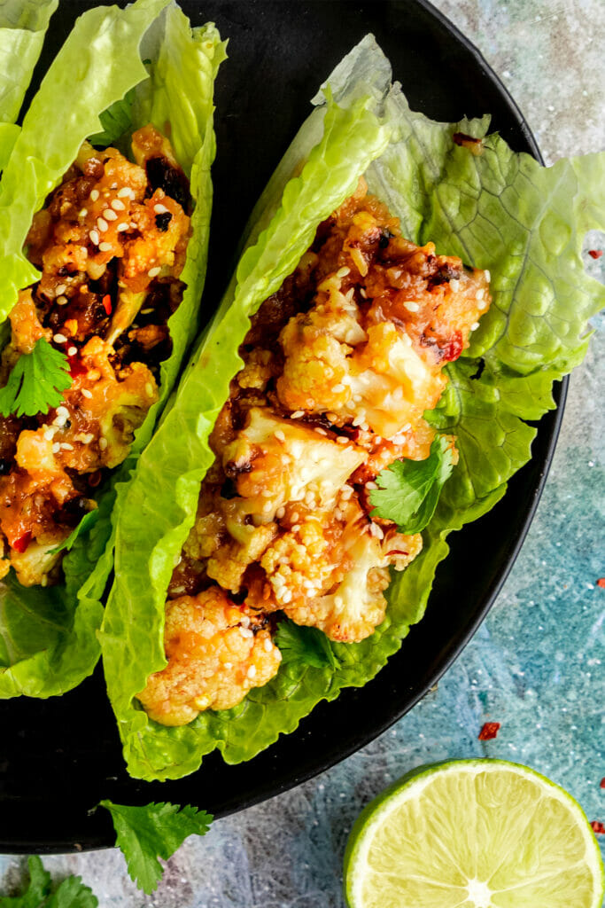 close up of sticky sesame cauliflower in a lettuce wrap topped with sesame seeds