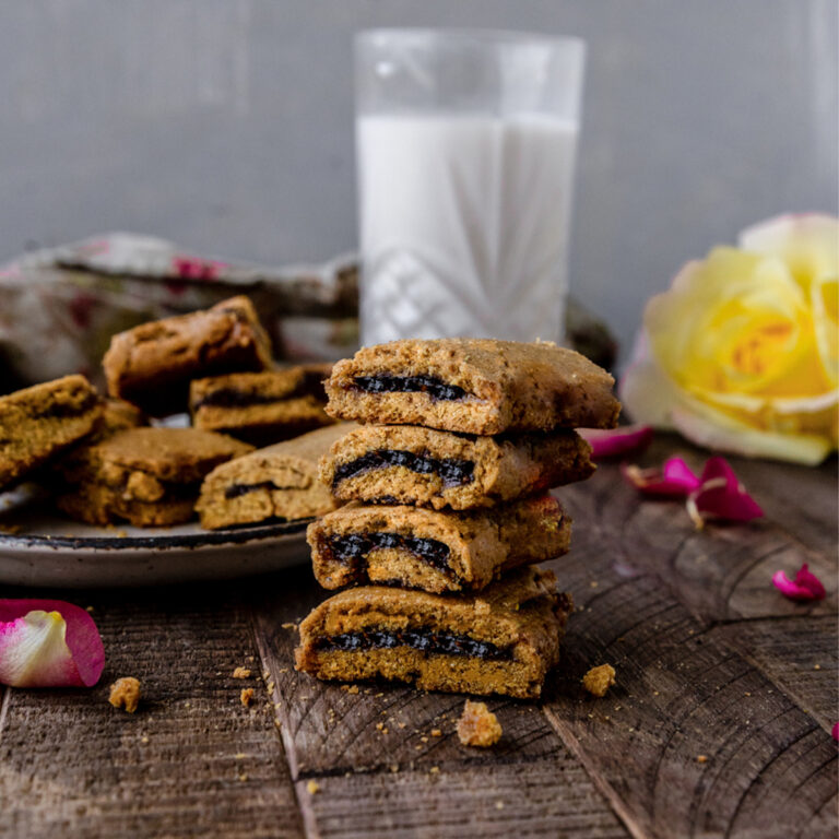 stack of homemade fig newton cookies next to a glass of milk