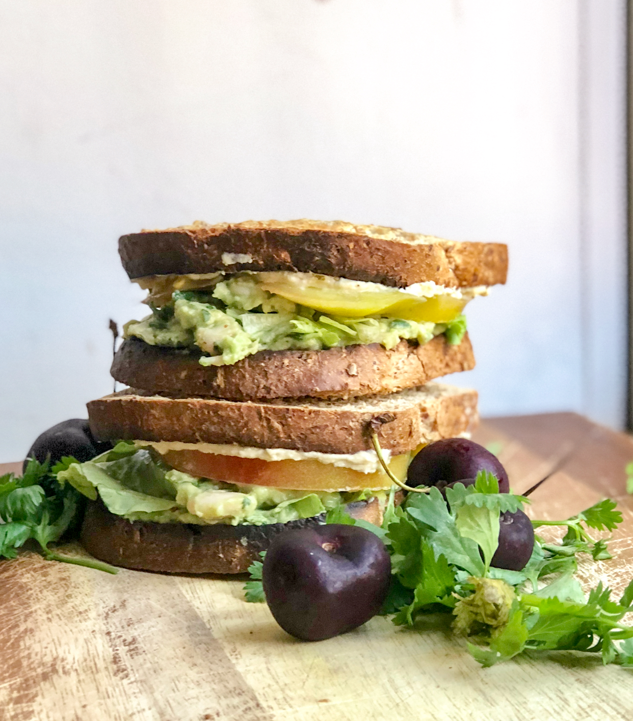 avocado white bean salad sandwich on a wooden board