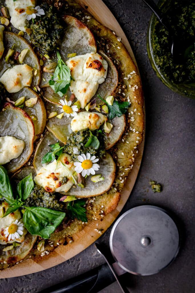 close up view of a crispy potato pesto pizza