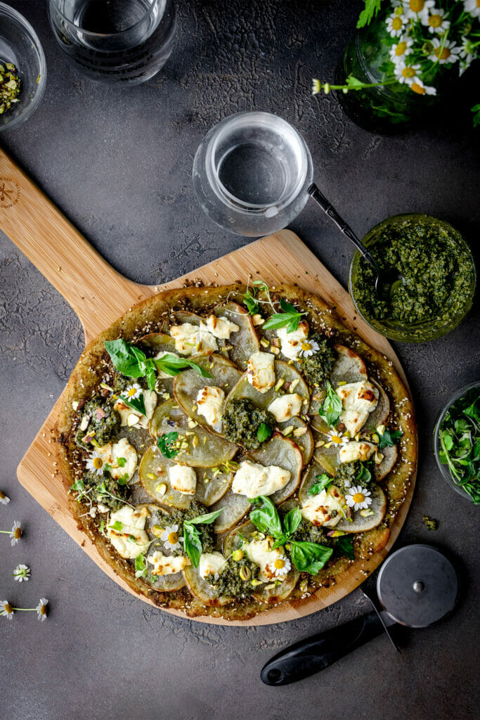 overhead shot of pesto potato pizza on a pizza peel next to a glass of water