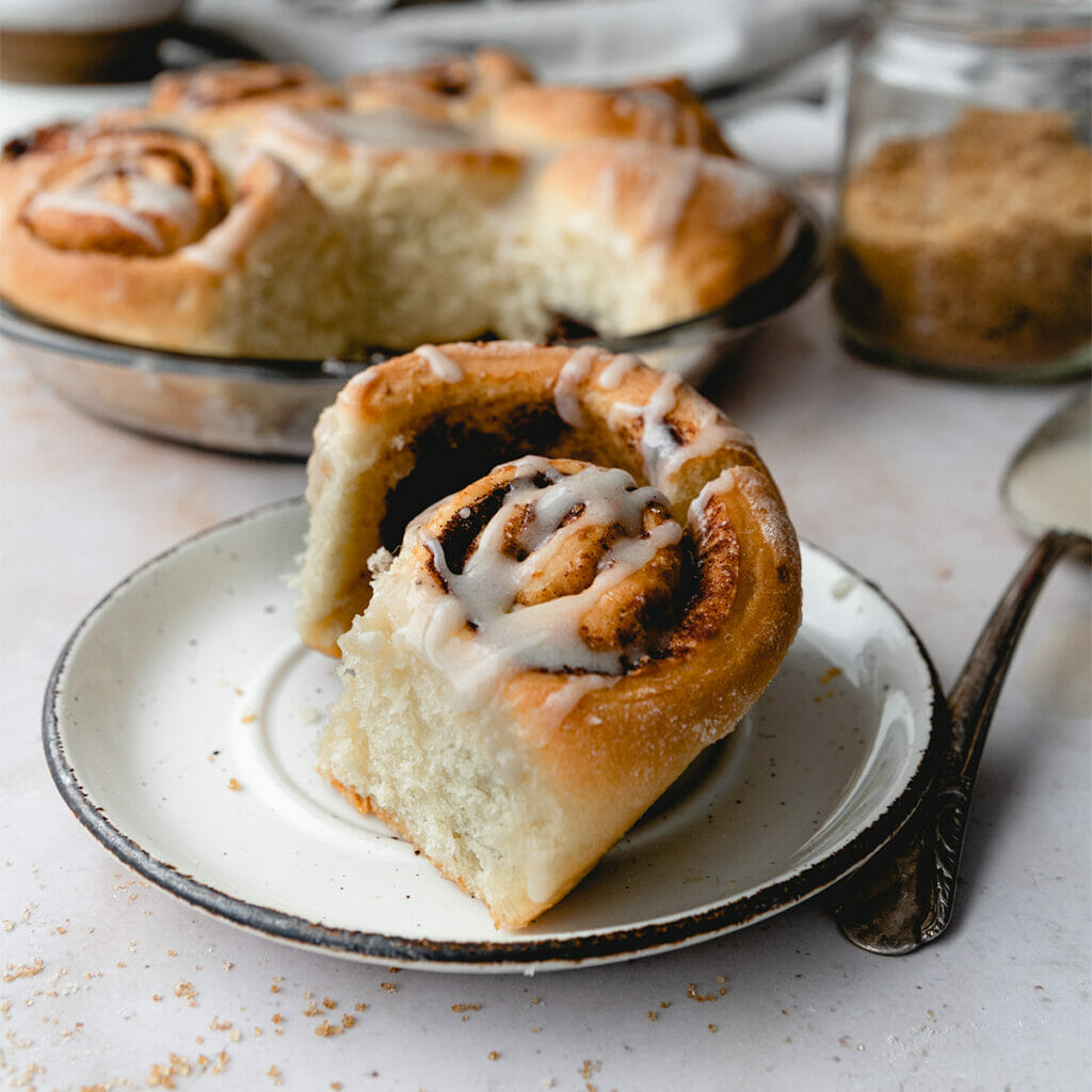 side view of quick cinnamon roll on a white plate with more in the background