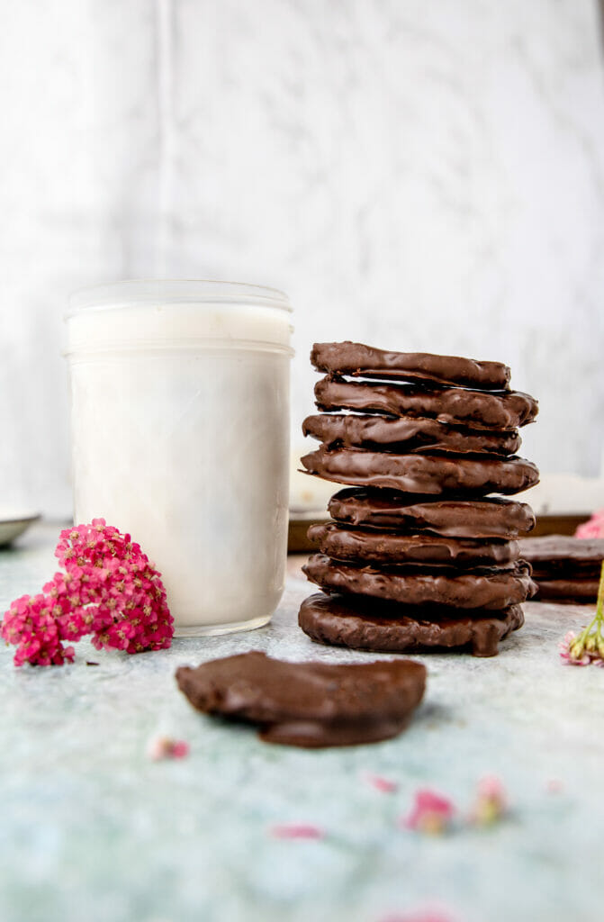 stack of vegan thin mint cookies next to a glass of milk and a pink flower