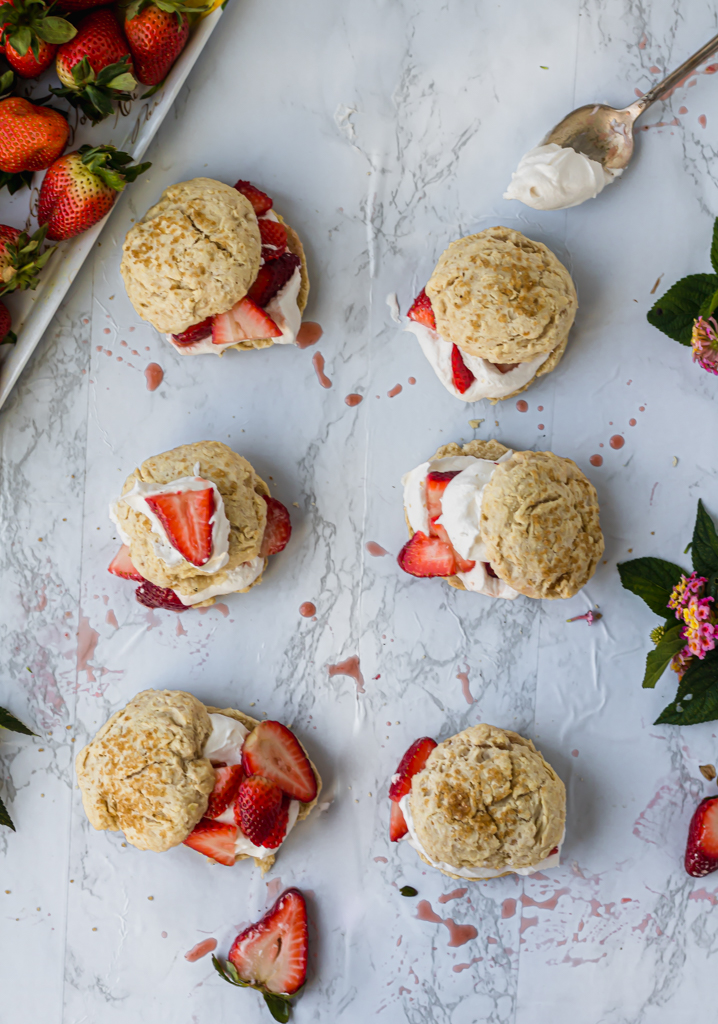 six vegan strawberry shortcakes on a marble board