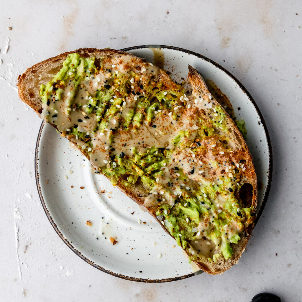 slice of tahini avocado toast on a white plate topped with old bay and everything bagel seasoning