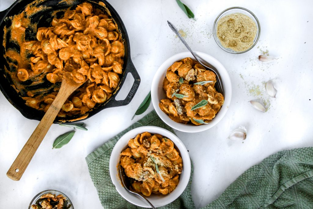two white bowls with pumpkin pasta
