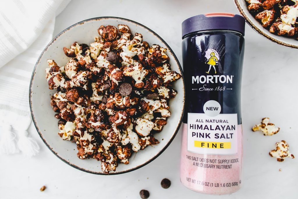 chocolate popcorn in a bowl next to morton's salt