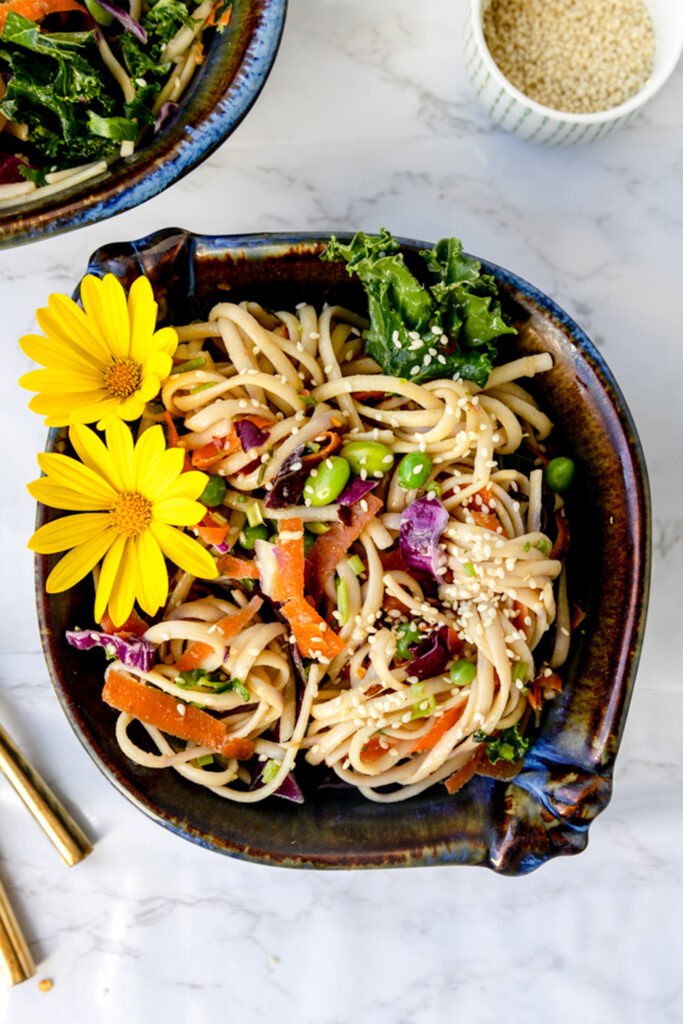 overhead shot of bowl of 15 minute sesame ginger noodles on a marble table with flowers