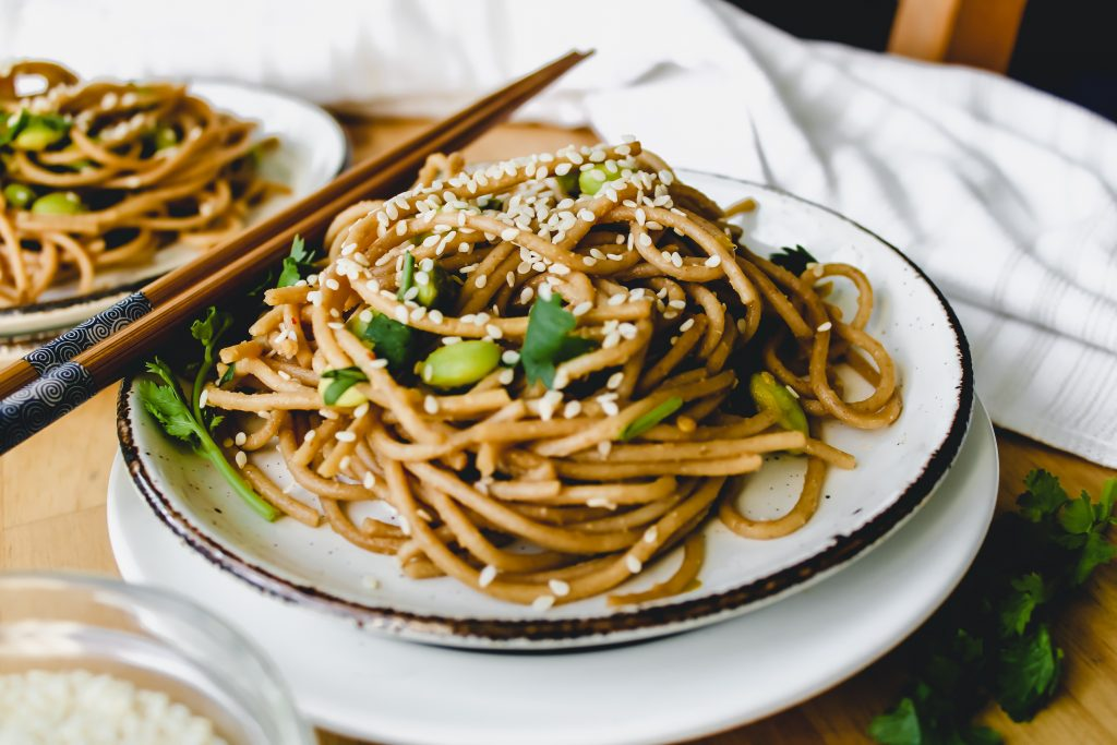 white plate of wheat noodles with sesame seeds on top