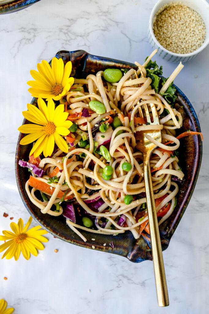 gold fork swirled into a blue ceramic bowl of sesame ginger noodles