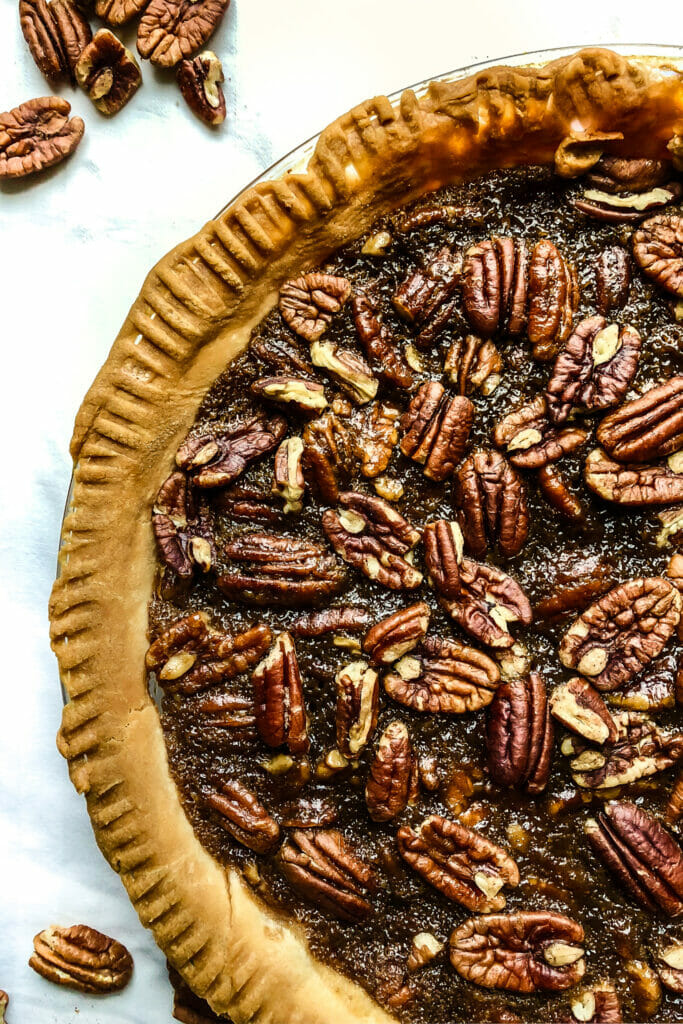 side birds eye view of vegan pecan pie in a pie plate on a white table