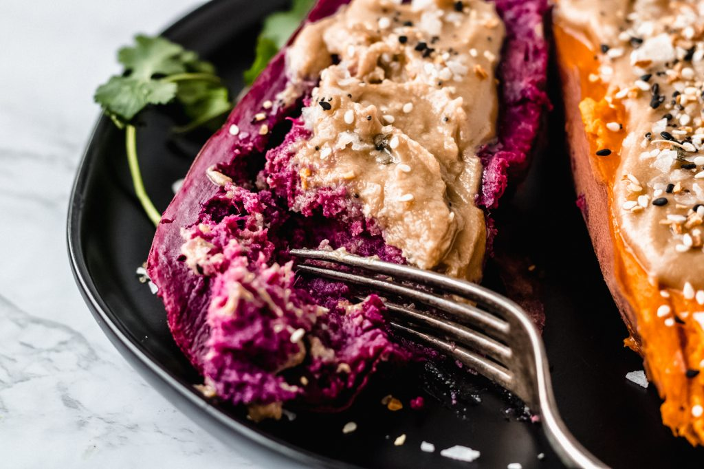 purple sweet potato on black plate with salt and tahini butter