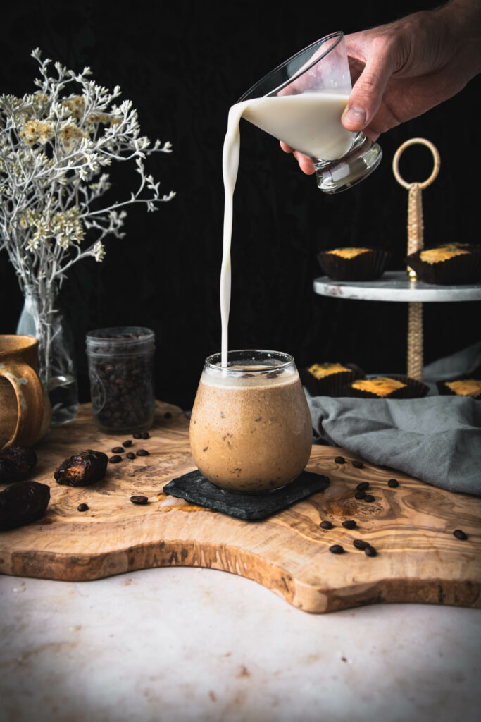 hand pouring milk into an iced coffee shake on a wooden table