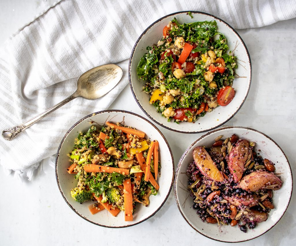 three bowls of quinoa salad with an antique spoon