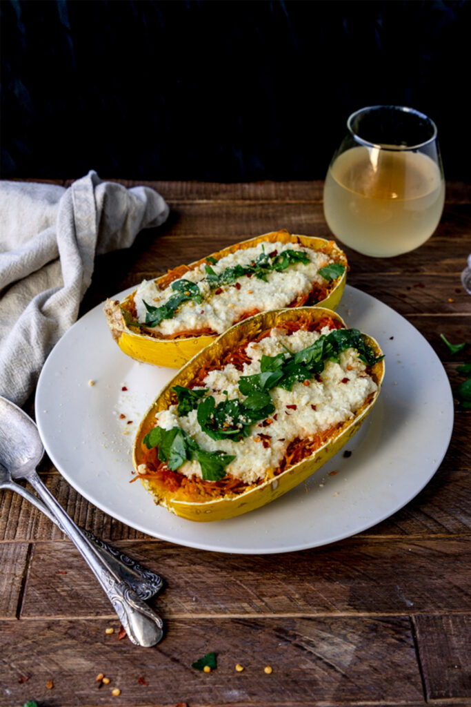 two spaghetti squash lasagnas with cashew cheese and topped with parsley on a white plate on a wooden table
