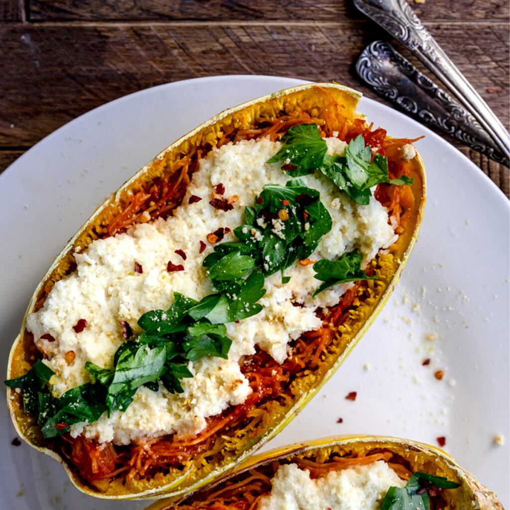 overhead shot of spaghetti squash lasagna boat on a white plate