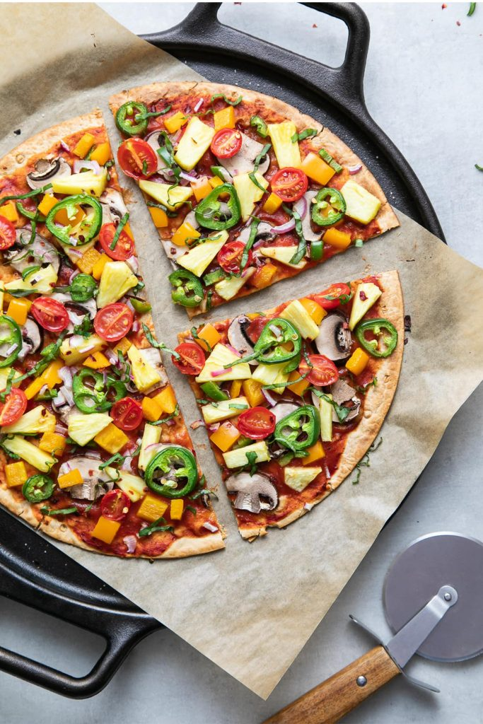 cast iron pan with parchment paper and sliced colorful veggie pizza