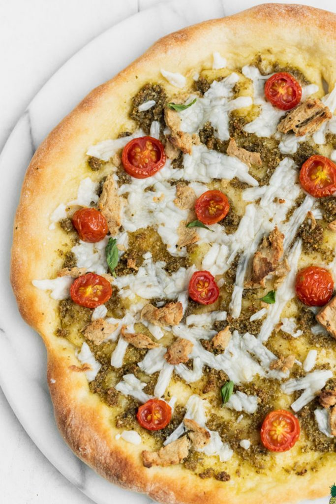 white pizza on plate with vegan chicken