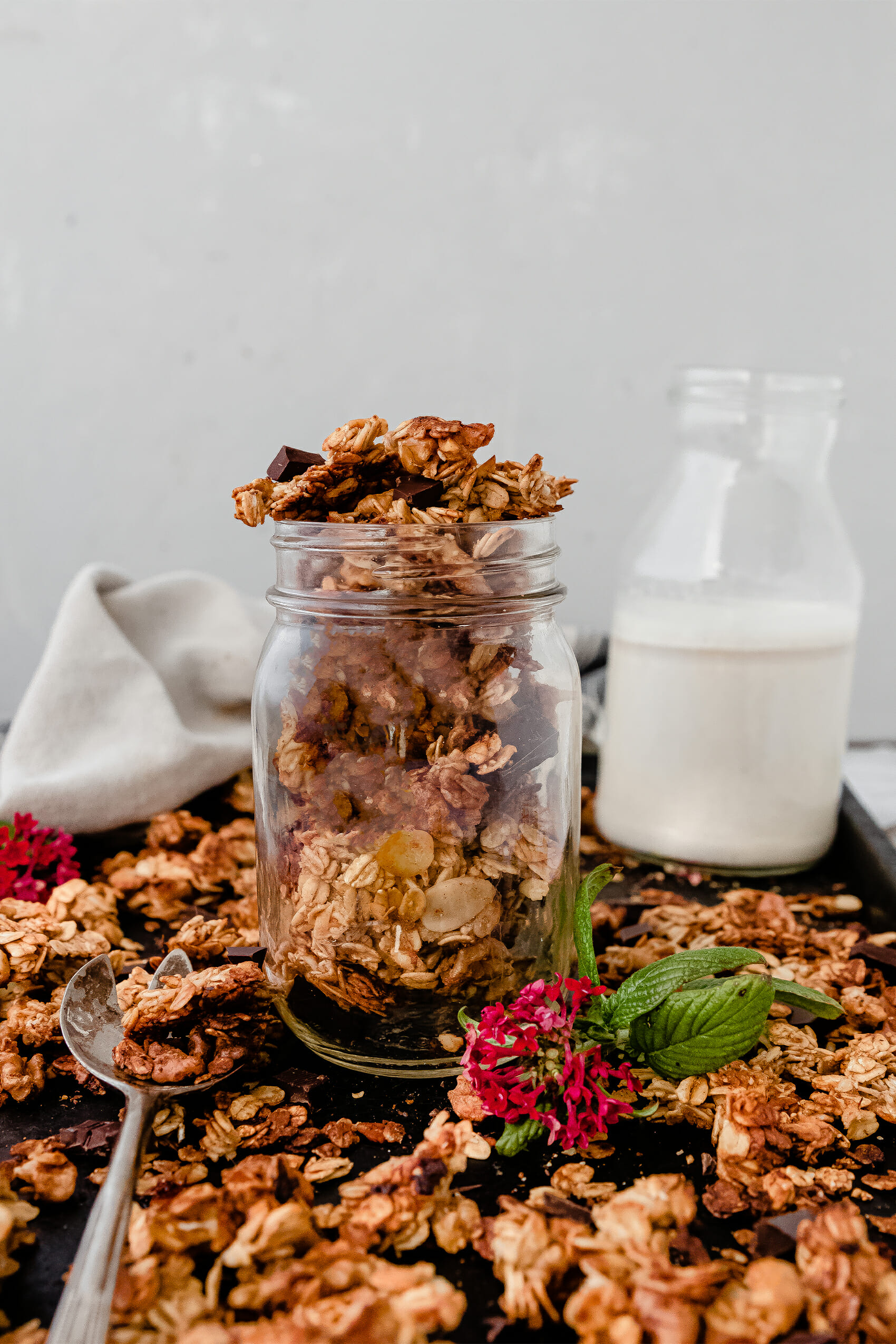 glass jar of banana bread granola on a tray next to a glass of milk