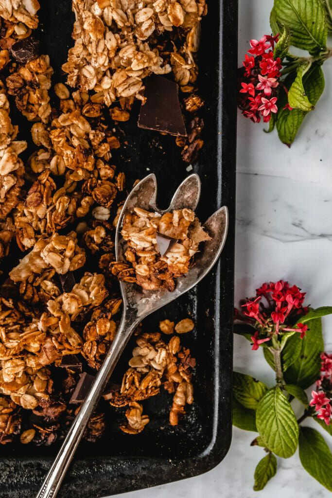 antique spoon scooping banana bread granola with chocolate chunks next to pink flowers