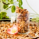 glass jar full of banana bread granola on a tray with an orange flower