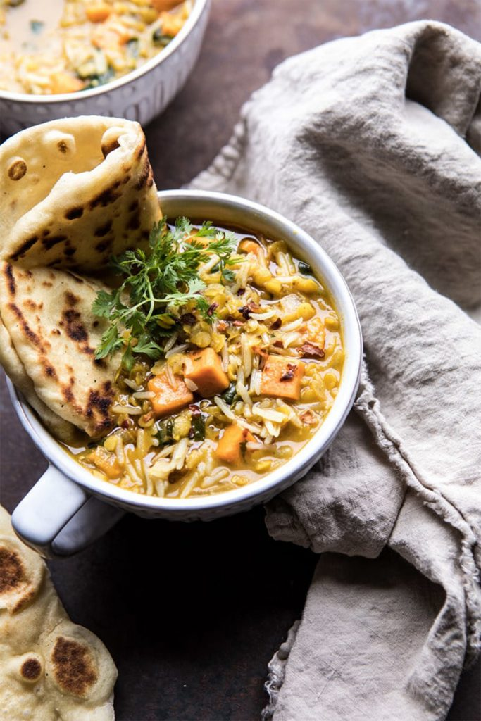 white bowl of yellow lentil soup with naan bread