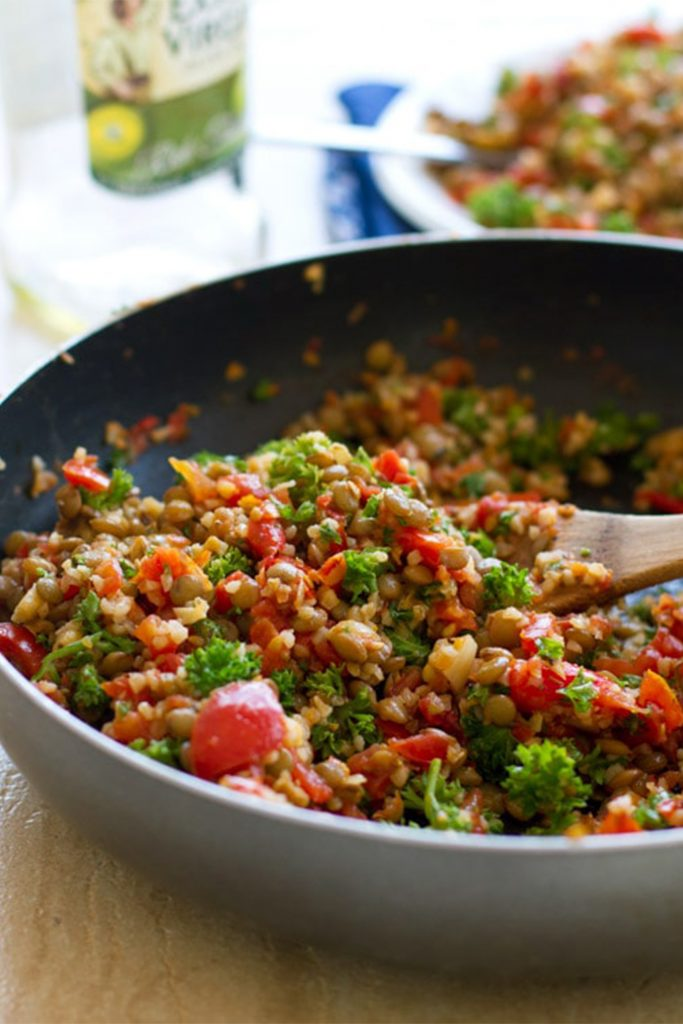 pan with lentil tomato salad and wooden spoon