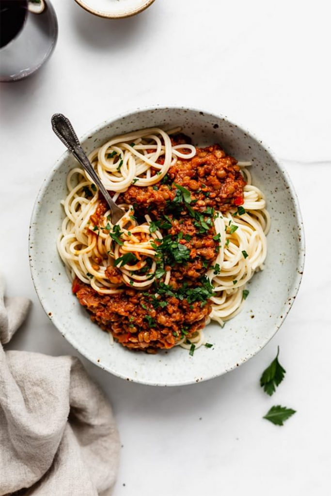 spaghetti in white bowl with red bolognese sauce
