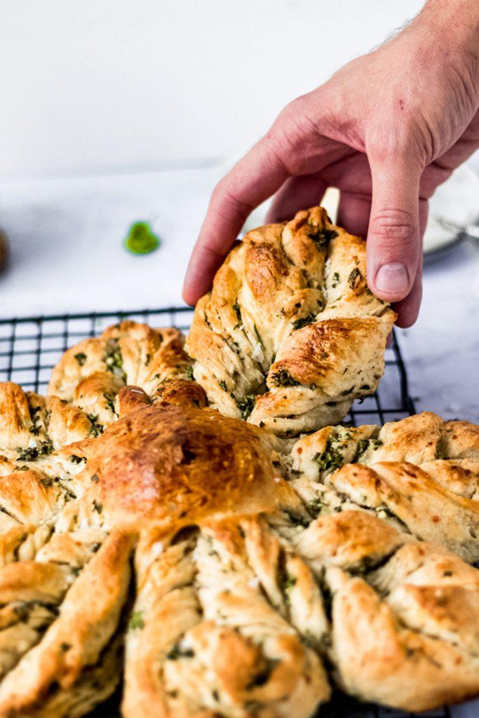 hand grabbing a piece of garlic star bread