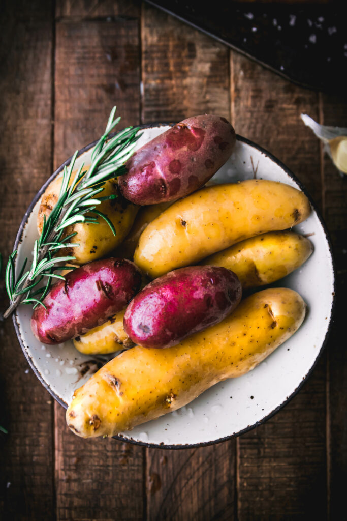 bowl of purple and white fingerling potatoes with rosemary