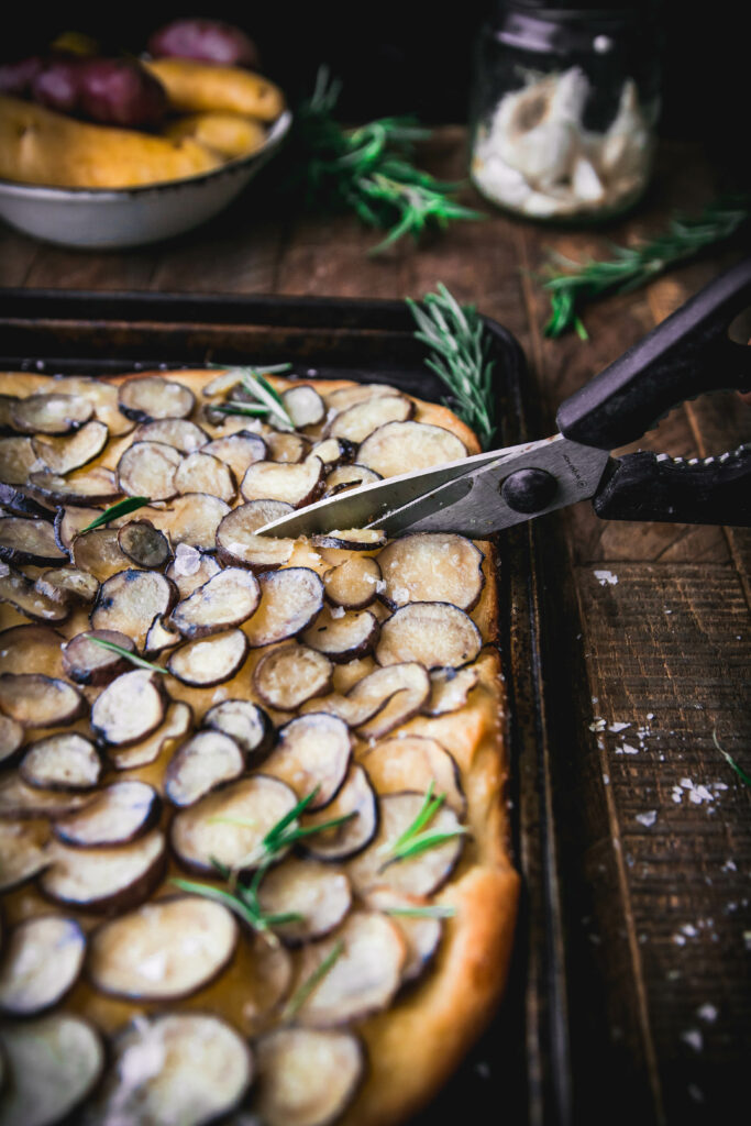 scissors cutting into rosemary potato focaccia