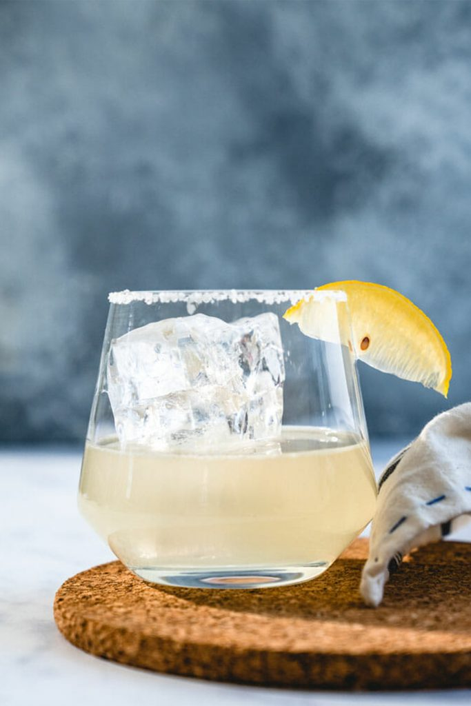 glass with large ice cube and lemon wedge