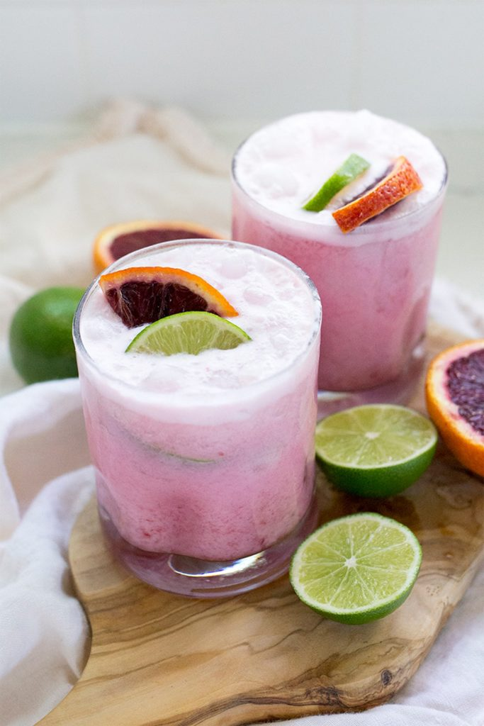 two short glasses of creamy purple margarita with orange wedges
