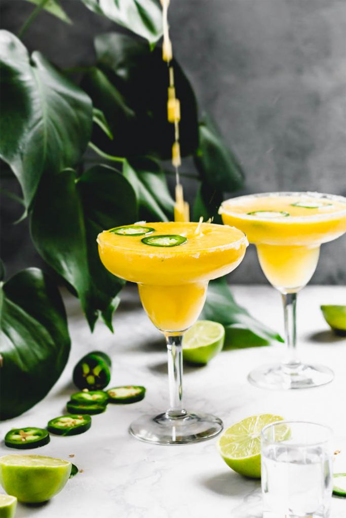pouring yellow mango margarita into a glass