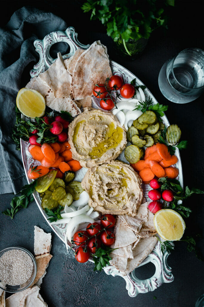 platter of creamy ottolenghi hummus surrounded by carrots, pickles, onions, pita, and cherry tomatoes with fresh herbs