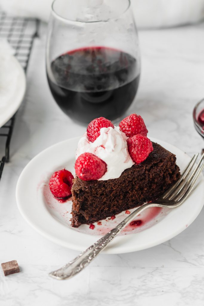 slice of vegan chocolate cake with glass of red wine in background