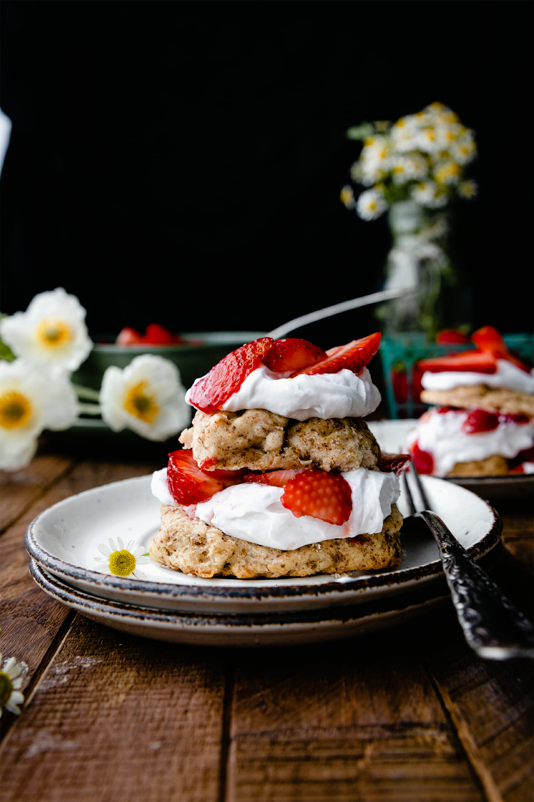 stack of vegan strawberry shortcake with whipped cream on a wooden table