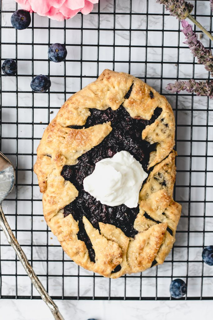 berry galette with yogurt topping on a marble sheet tray