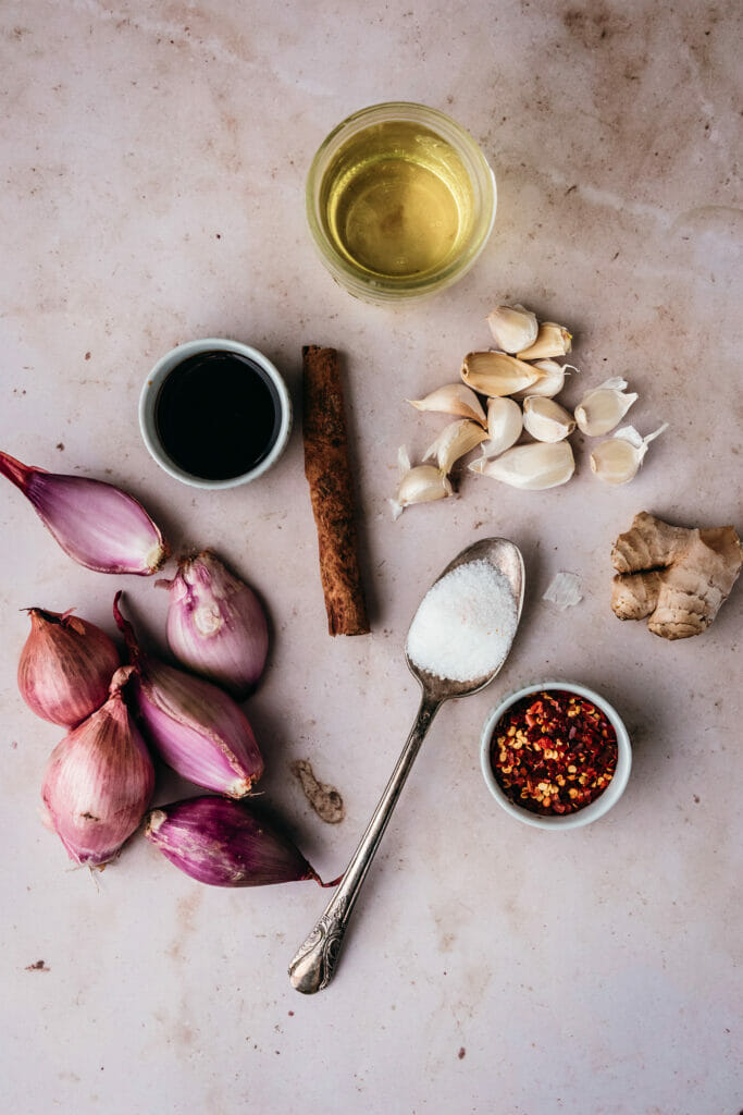 overhead shot of ingredients needed for chili crisp - shallots, cinnamon, soy sauce, sugar, oil, garlic, ginger, and red pepper flakes