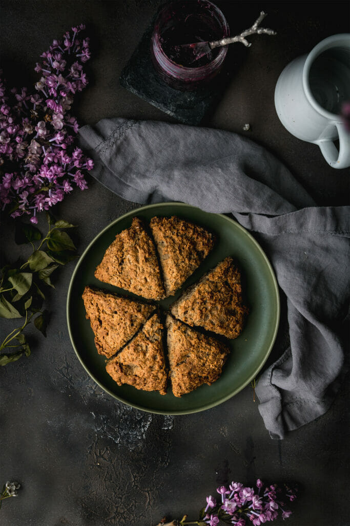 Ovehead shot of plate of vegan scones next to a lilac