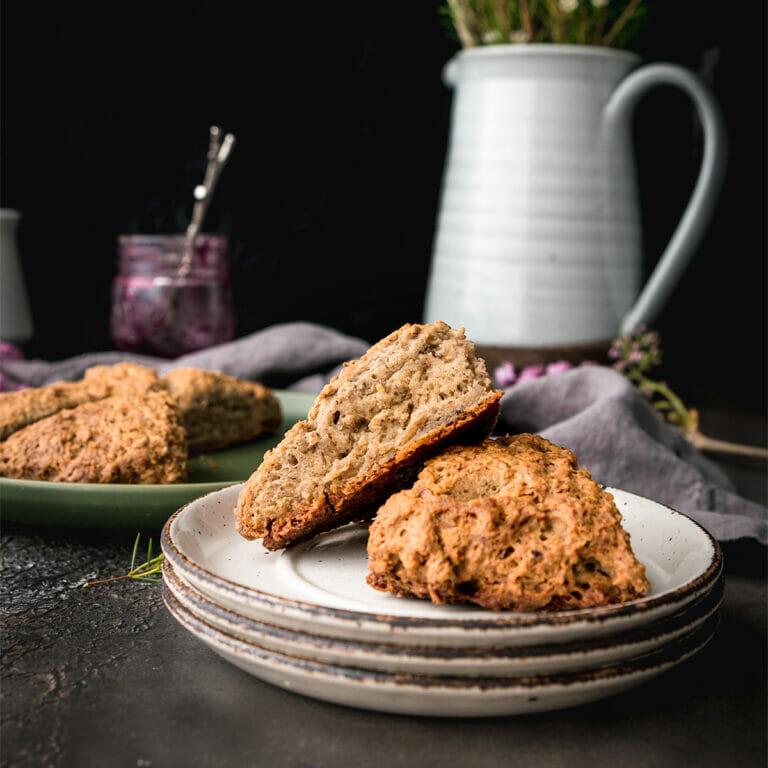 plate of two vegan scones next to a jar pf jam