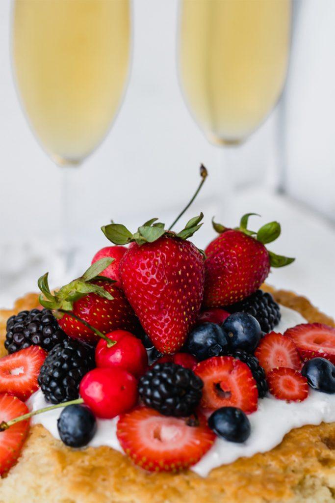 pile of strawberries, blackberries, blueberries, and cherries on a vegan white cake