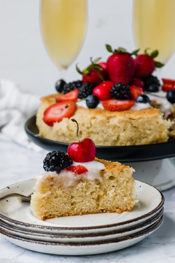 slice of white olive oil cake topped with berries with champagne in the background