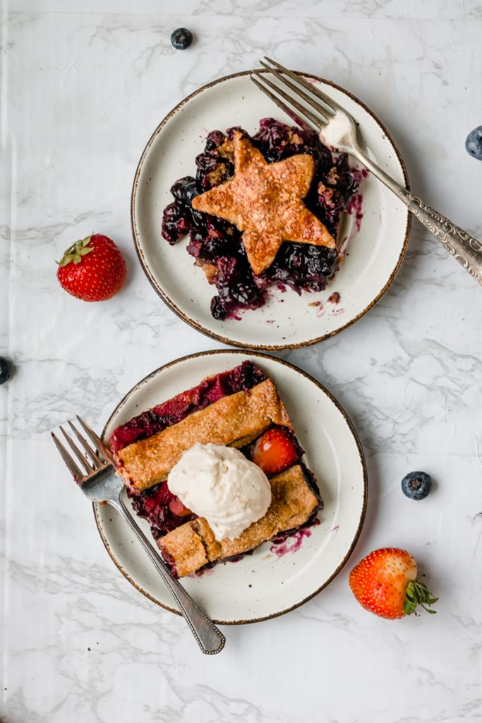 two slices of vegan pie on white plates with berries