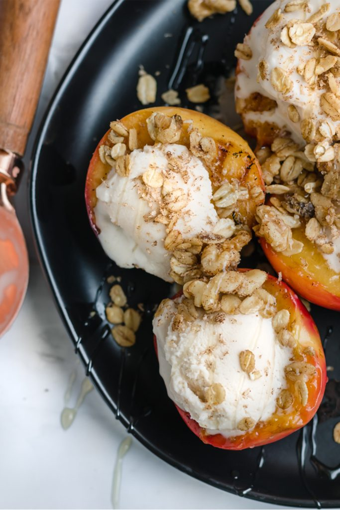 grilled peaches on a plate with cinnamon crispies