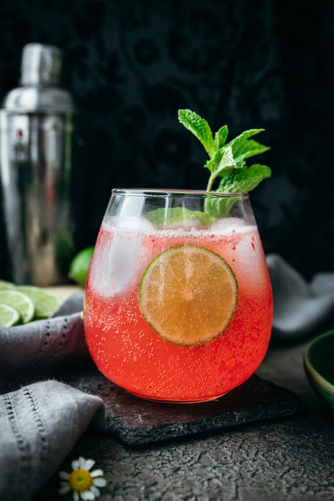 side view of strawberry limeade with a lime circle and a sprig of mint