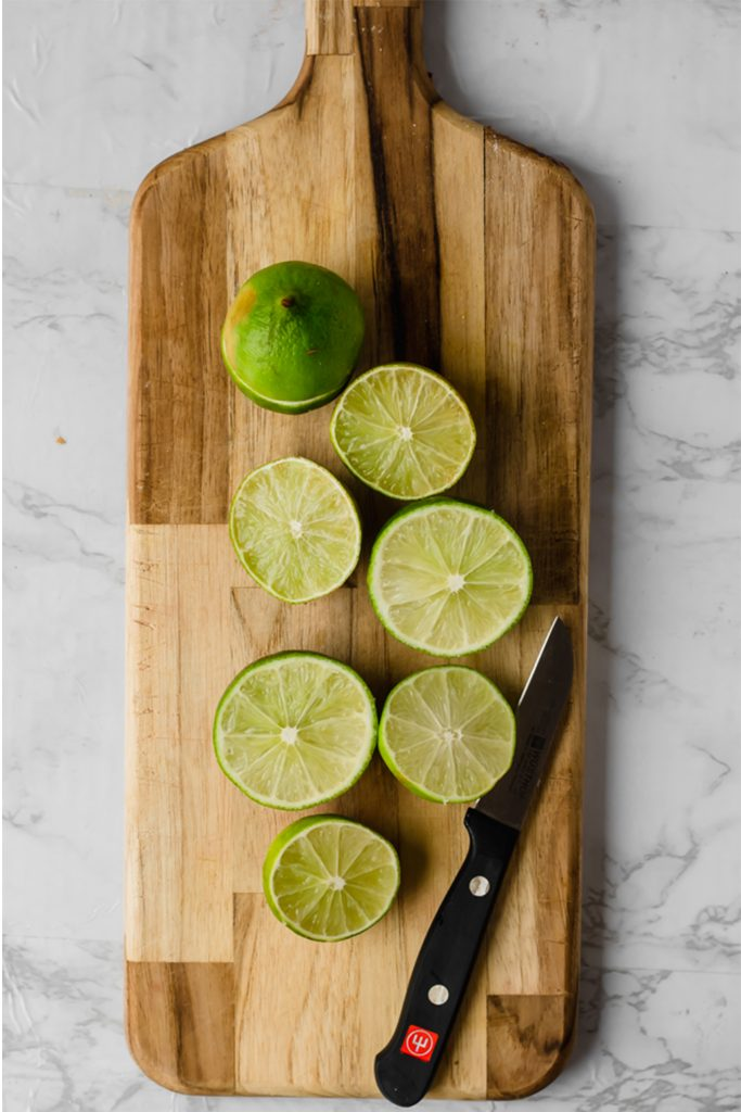 wooden cutting board with 4 limes sliced in half, next to a paring knife