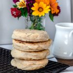 stack of vegan english muffins on a sheet tray with a vase of flowers in the background