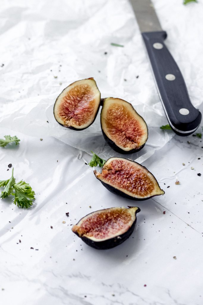 sliced figs on a white board with a knife in the foreground
