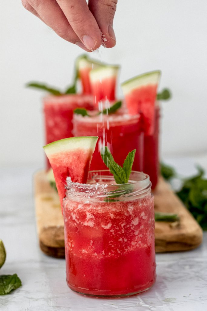 salted watermelon margaritas on a marble board with mint sprigs